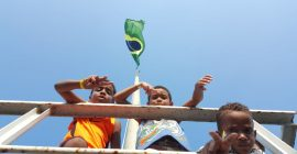 Looking up at 3 boys on EduMais's After-School Program at Leme fort who points towards the camera with Brazil flag and blue sky