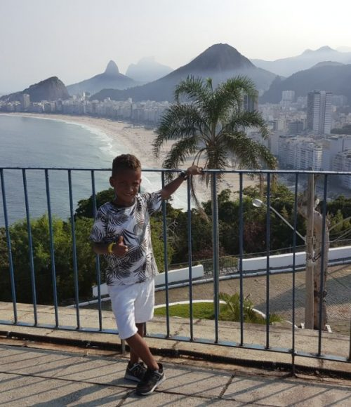 EduMais After-School Program student Renee at Leme fort with view of Copacabana and Rio de Janeiro's hills in the background