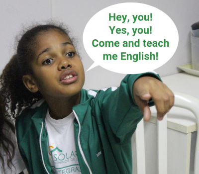 Volunteering advert with EduMais student pointing and calling for volunteers to teach her English