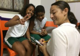 EduMais volunteer English teacher Sally makes the classroom rules with two EduMais students, one making a peace sign