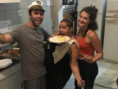 Man and two women with a plate of food in the kitchen