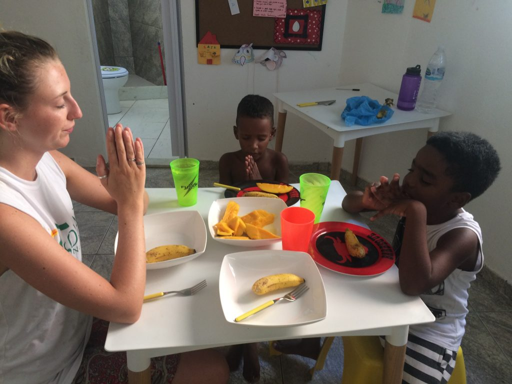 EduMais volunteer Eva and two boys on our after-school program give thanks before a snack of mango and bananas