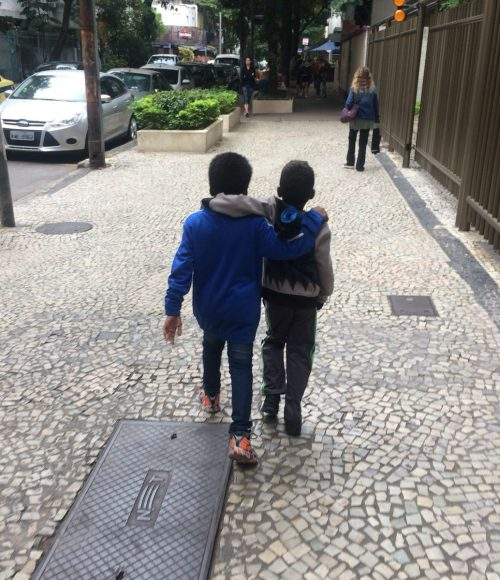 EduMais after-school program students Andre and Renee walk down a street in Ipanema with their arms around each other