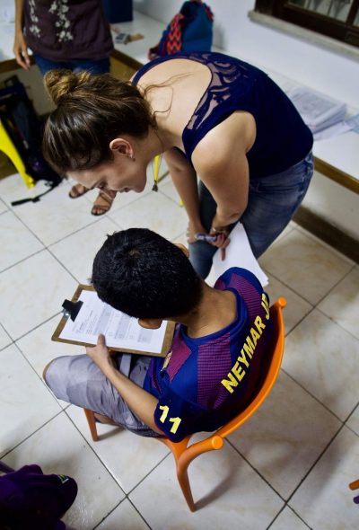 EduMais volunteer English teacher Nikola helps out a student with his work over his shoulder
