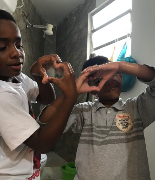 EduMais after-school program students Andre and Romulo form heart shapes with their hands