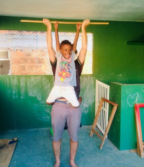 EduMais after-school volunteer Ed lifts student Renee into the air on a wooden stick
