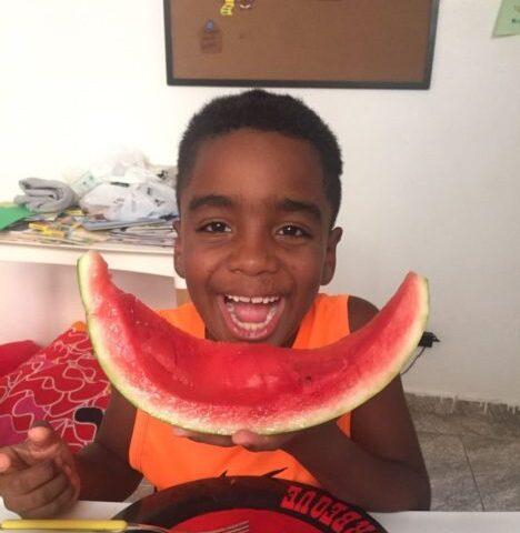 Black boy eating healthy food at NGO in favela in rio de Janeiro