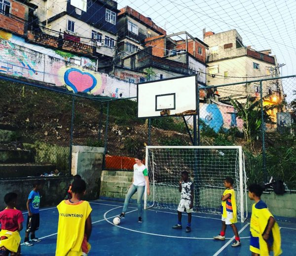 EduMais volunteer Iris plays football with kids on the pitch with houses of the Cantagalo favela visible in the background