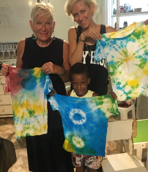 EduMais volunteer Hannah, her aunt, and one of the after-school boys pose with their tie-dye t-shirts