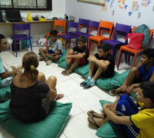 EduMais Programming Camp students sit on green cushions with their volunteer teacher Roger and EduMais founder Diana NIjboer