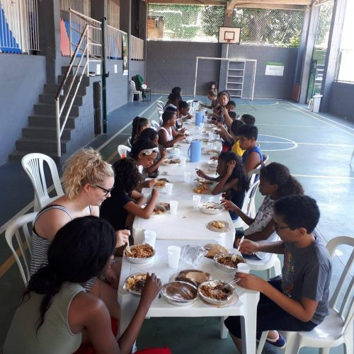 Students and volunteers at EduMais's English Summer Camp 2019 sit at long white tables having lunch
