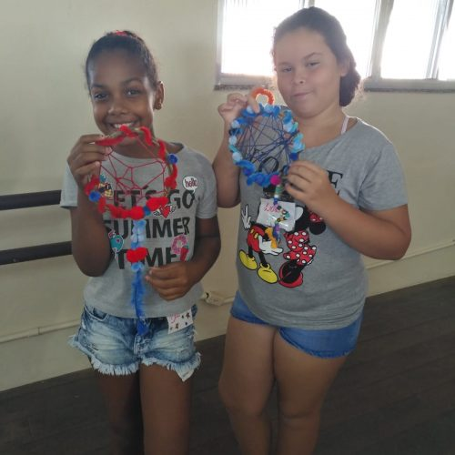 Two of EduMais's girl students display the dreamcatchers they made at EduMais's English Summer Camp 2019