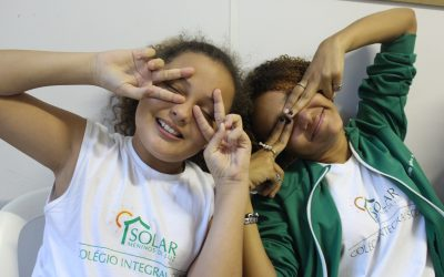 Two of EduMais's girl students make peace signs over their eyes in the classroom