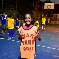 EduMais student Nicolle poses for the camera on the football pitch