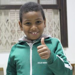 Young smiling boy thumb up in classroom
