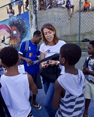 EduMais founder Diana Nijboer and William give out rucksacks donated by WINGS foundation
