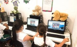 Two EduMais girl students work on their computers on the Web Design Program with cuddly toys on top of the computers