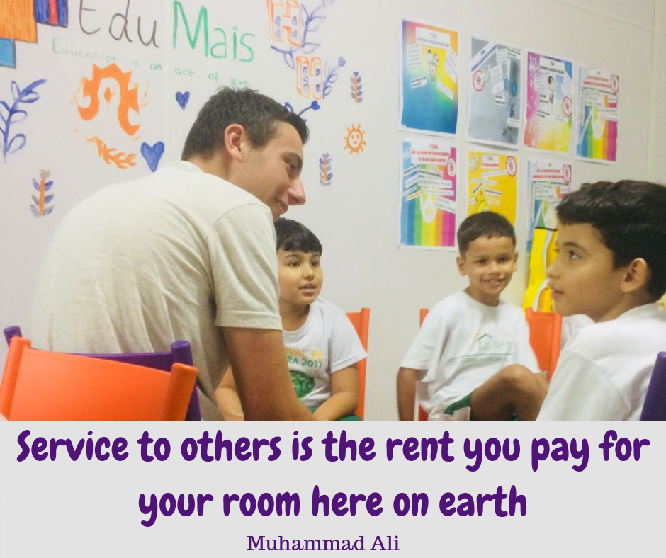 EduMais volunteer Hamish with EduMais students and Muhammad Ali quote about service to others