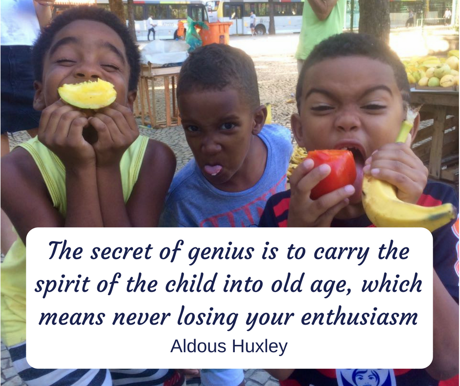 Boys on After-School Program pose with various fruits with Aldous Huxley quote about the spirit of the child overlaid on image