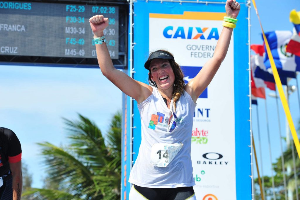 EduMais volunteer Anna Bowman cross the Ironman finish line with her arms raised in celebration