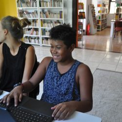 EduMais Summer Camp Program student Eryc smiling in front of a laptop in the Solar Menions de Luz library