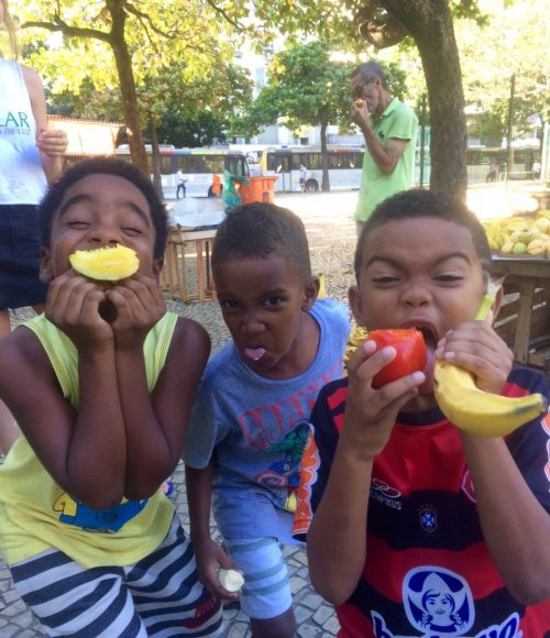 EduMais after-school program boys make funny faces while holding up various different fruits
