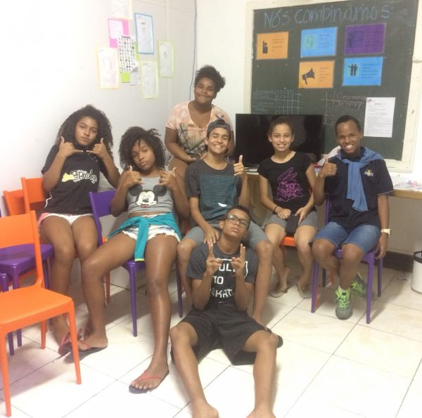 Students on EduMais's Community English Class pose in the classroom with their thumbs up