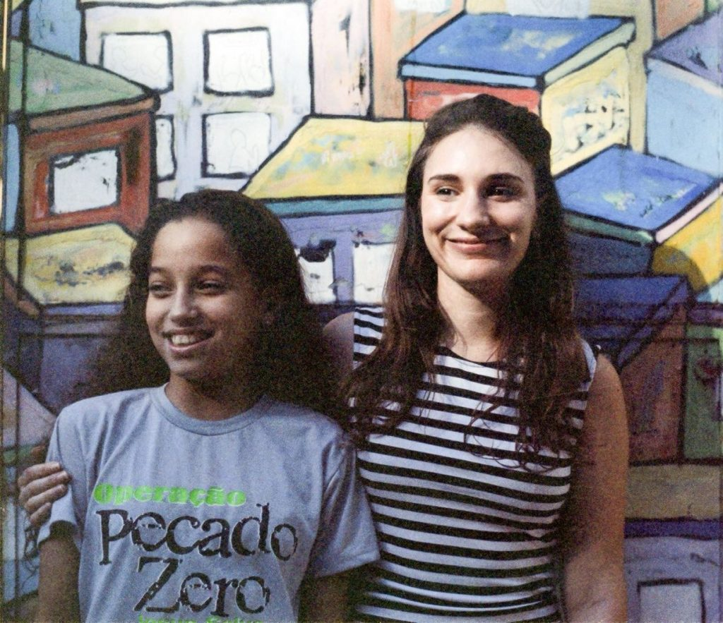 Volunteer English teacher Nikola with arm round one of her students Izabely in front a colourful favela mural