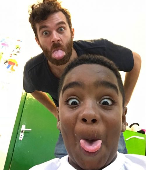 Volunteer Ed and after-school program student Andre take a selfie with their tongues sticking out