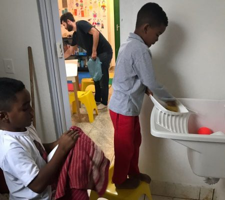 EduMais after-school students wash up their plates while volunteer Ed tidies the room in the background