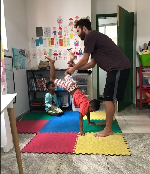 EduMais after-school program student Romulo attempts a handstand with volunteer Ed holding his legs in support