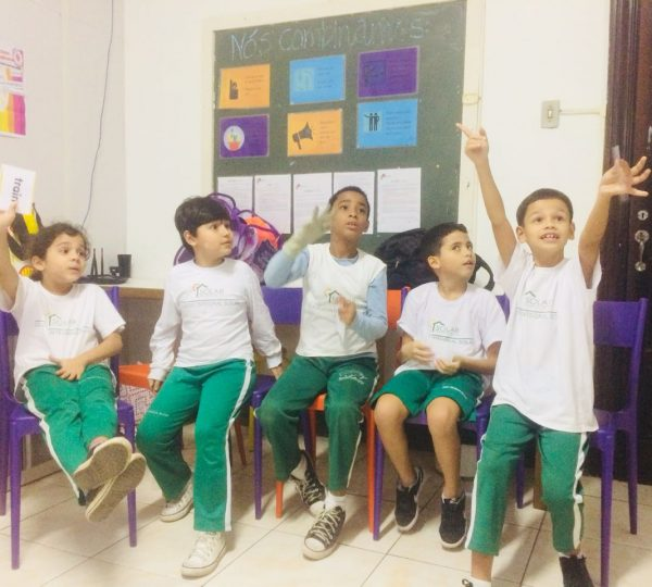 EduMais English students desperate to answer the teacher's question and one boy even stands up from his chair in excitement