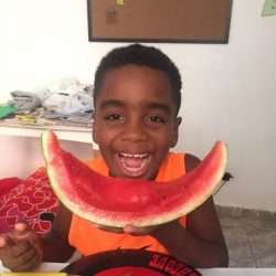 EduMais after-school program student Andre grins widely with an eaten segment of a watermelon