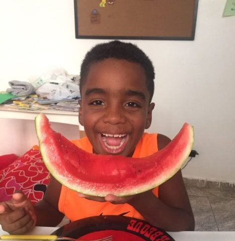 Black boy eating healthy food at NGO in favela in rio de Janeiro
