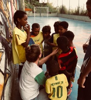 EduMais volunteer Iris squats down to talk with the students on the football program who surround her
