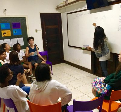 Volunteer English teacher Rebeka points at the whiteboard with the extracurricular English group in the EduMais classroom