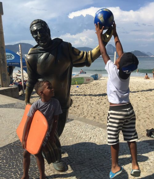 One of EduMais's after-school boys jumps to put a football in the hand of the Dorival Caymmi statue on Copacabana Beach