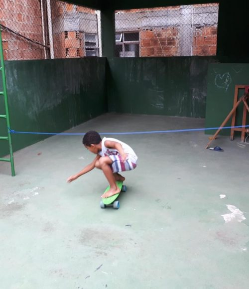 One of EduMais's after-school students plays a game of skateboard limbo