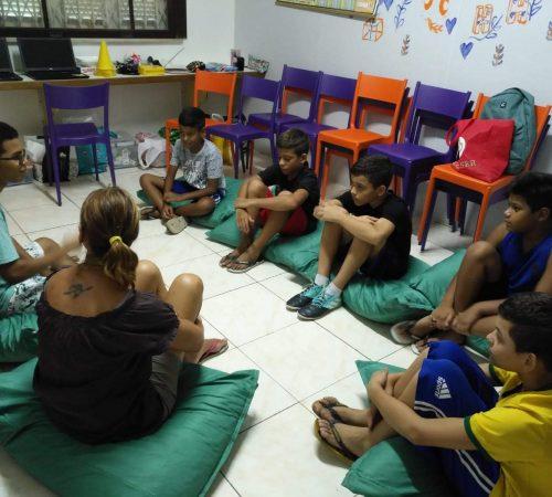 EduMais Programming Camp students sit on green cushions with their volunteer teacher Roger and EduMais founder Diana NIjboer