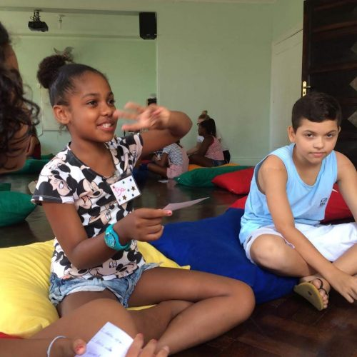 A girl student at EduMais's English Summer Camp 2019 holds up three fingers as she begins a game of 2 truths and a lie