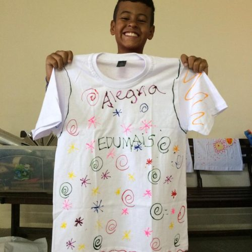 Student at EduMais's English Summer Camp holds up a t-shirt he designed with the word alegria (happiness)
