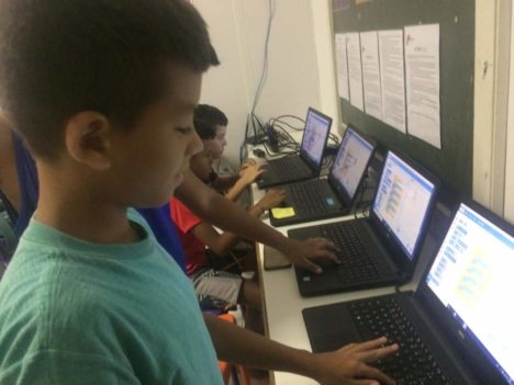 Kids on laptops using scratch game design