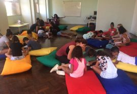 Layout of English Summer Camp learning space with students, volunteers, and big, colourful cushions