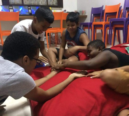 Boys at EduMais's Programming Camp 2019 sit in a circle and stretch out all their hands to touch in the middle with their volunteer teacher Roger