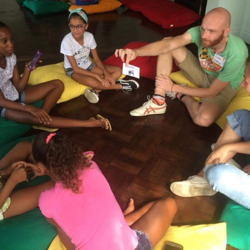 EduMais volunteer Coen holds up a flashcard for a group of students sat on colourful cushions at English Summer Camp 2019