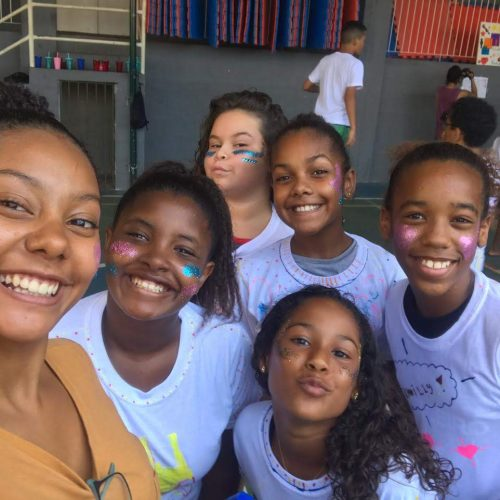 5 girls at EduMais's Summer Camp 2019 and volunteer Thais take a selfie with their cheeks covered in multicoloured glitter