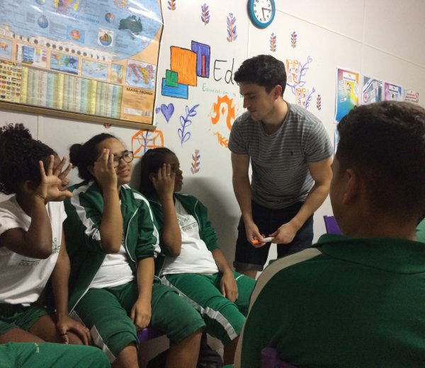 EduMais volunteer teacher Donal in the classroom with three EduMais girl students who hold their hands to their heads