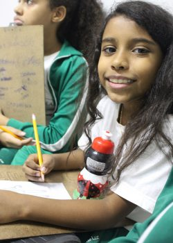 EduMais student smiles for the camera while working with a pencil and paper on her English skills