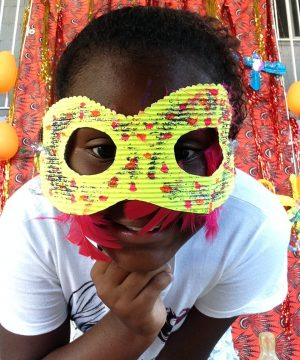 One of EduMais's Summer Camp students with a yellow mask over a lot of her face