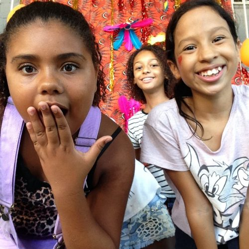 Three of EduMais's Summer Camp girls, two smiling, one with hand over her mouth as if in shock